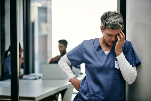 A nurse leans against the wall after a bad injury